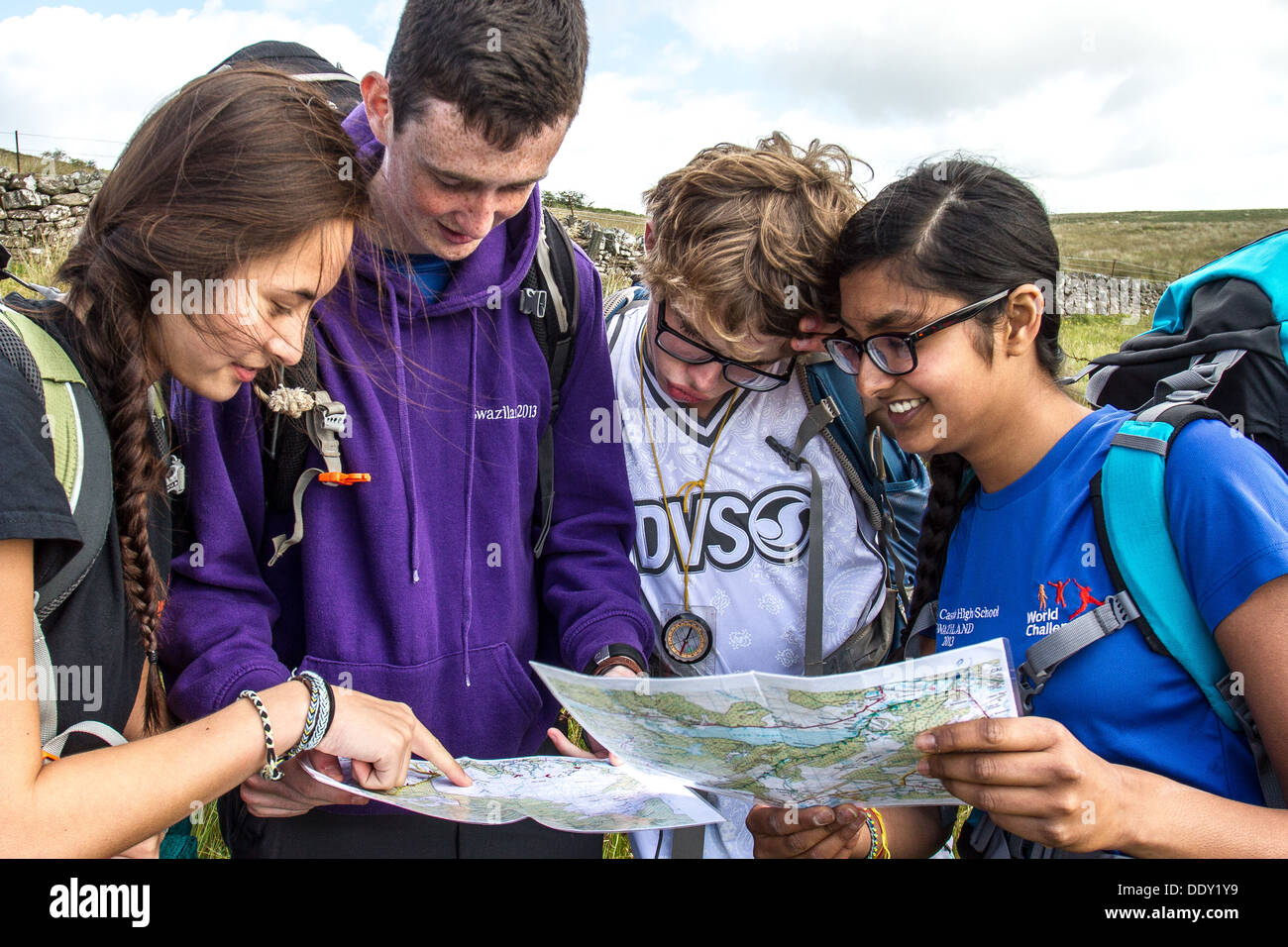 A mixed group of young people read a map and navigate in the countryside - Stock Image