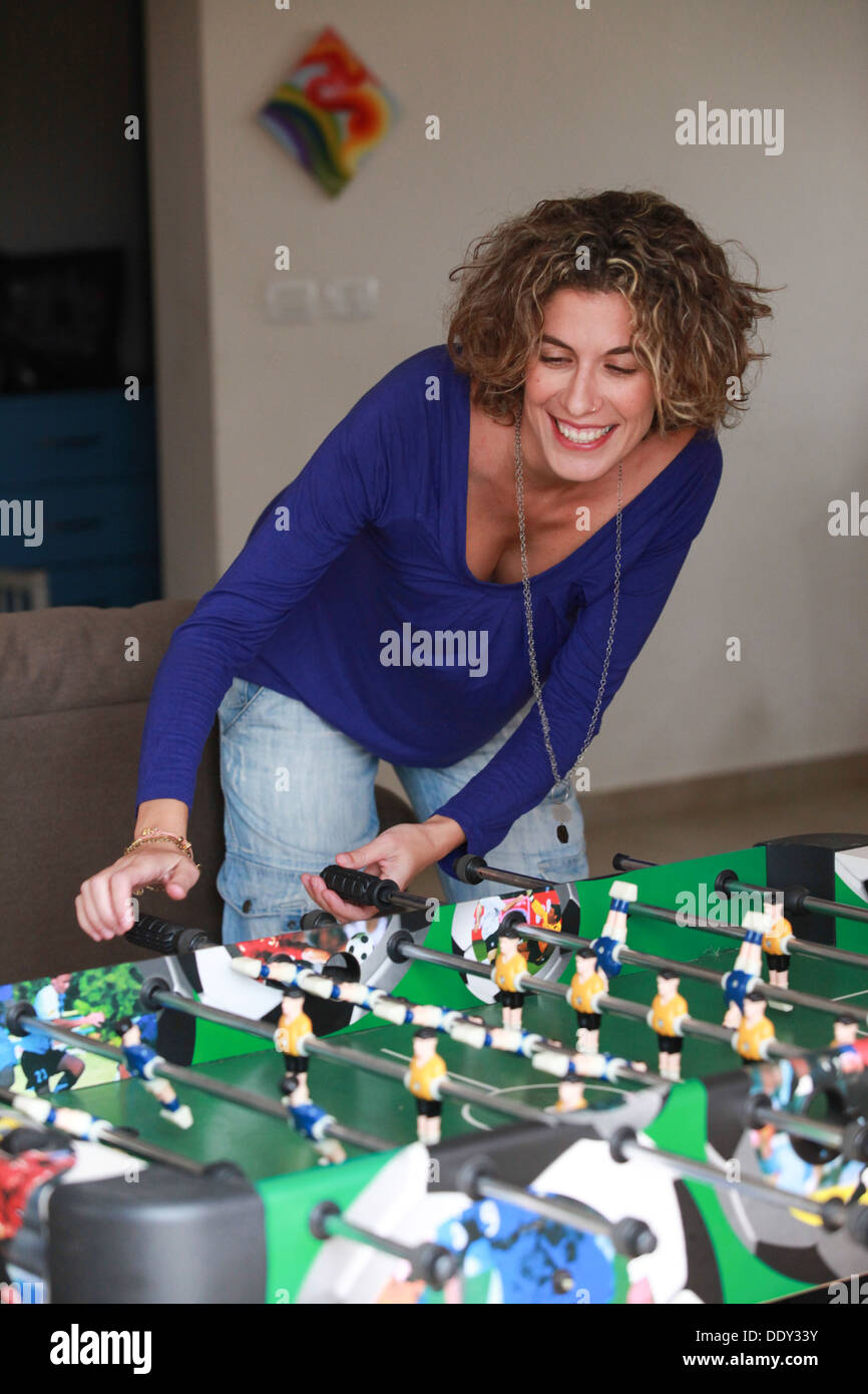 Young woman plays foosball (Table football)  - Stock Image