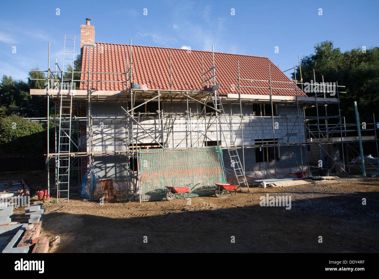 Scaffolding around new detached house building site - Stock Image