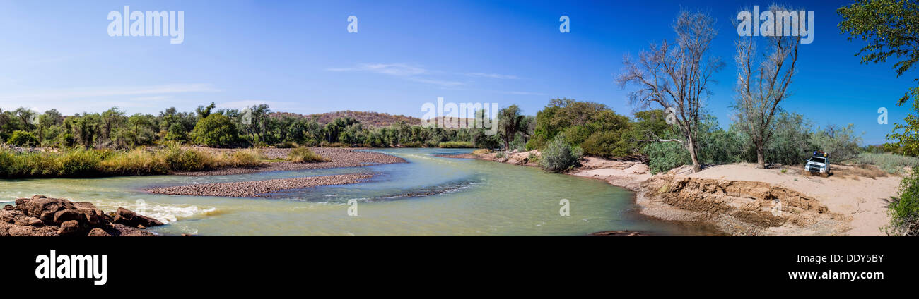 Off-road vehicle parked beside the Kunene River - Stock Image