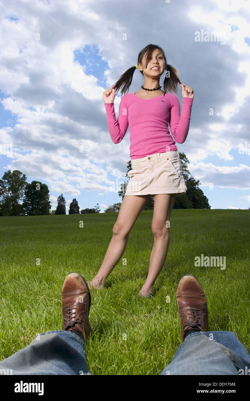 Young Spanish/Asian woman, in pigtails, and a man´s legs and feet, posing  at a park