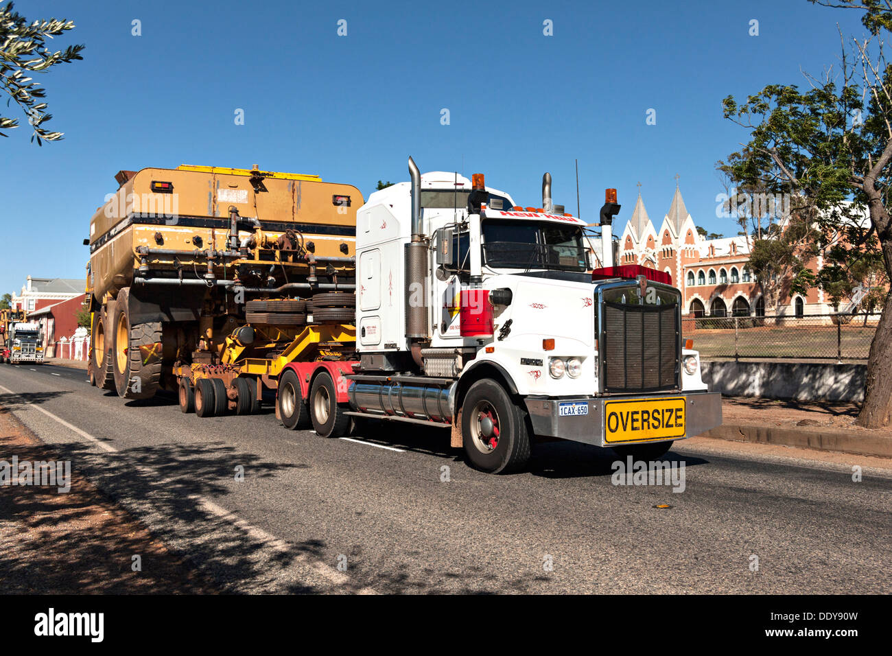 Truck with oversize load passing St IIdephonsus Monastery, New Norcia Western Australia - Stock Image