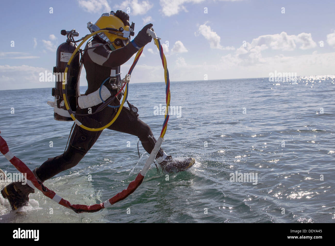 A US Navy technical diver performs a front step-in water entry during dive training operations January 16, 2013 in Key West, FL. - Stock Image
