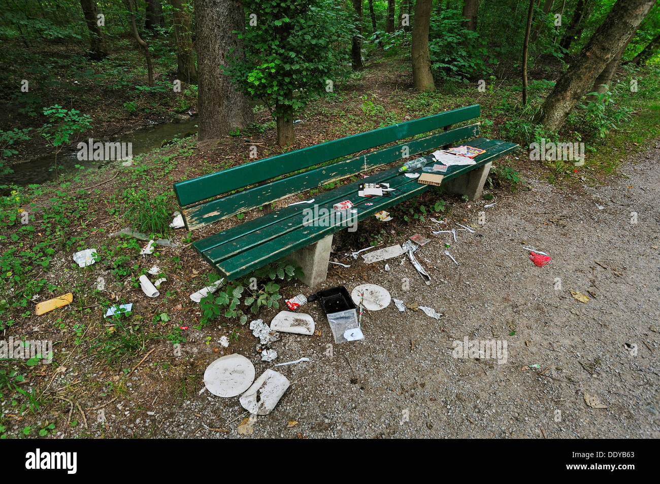 Park bench with garbage in the Isarauen floodplain, Munich, Bavaria - Stock Image