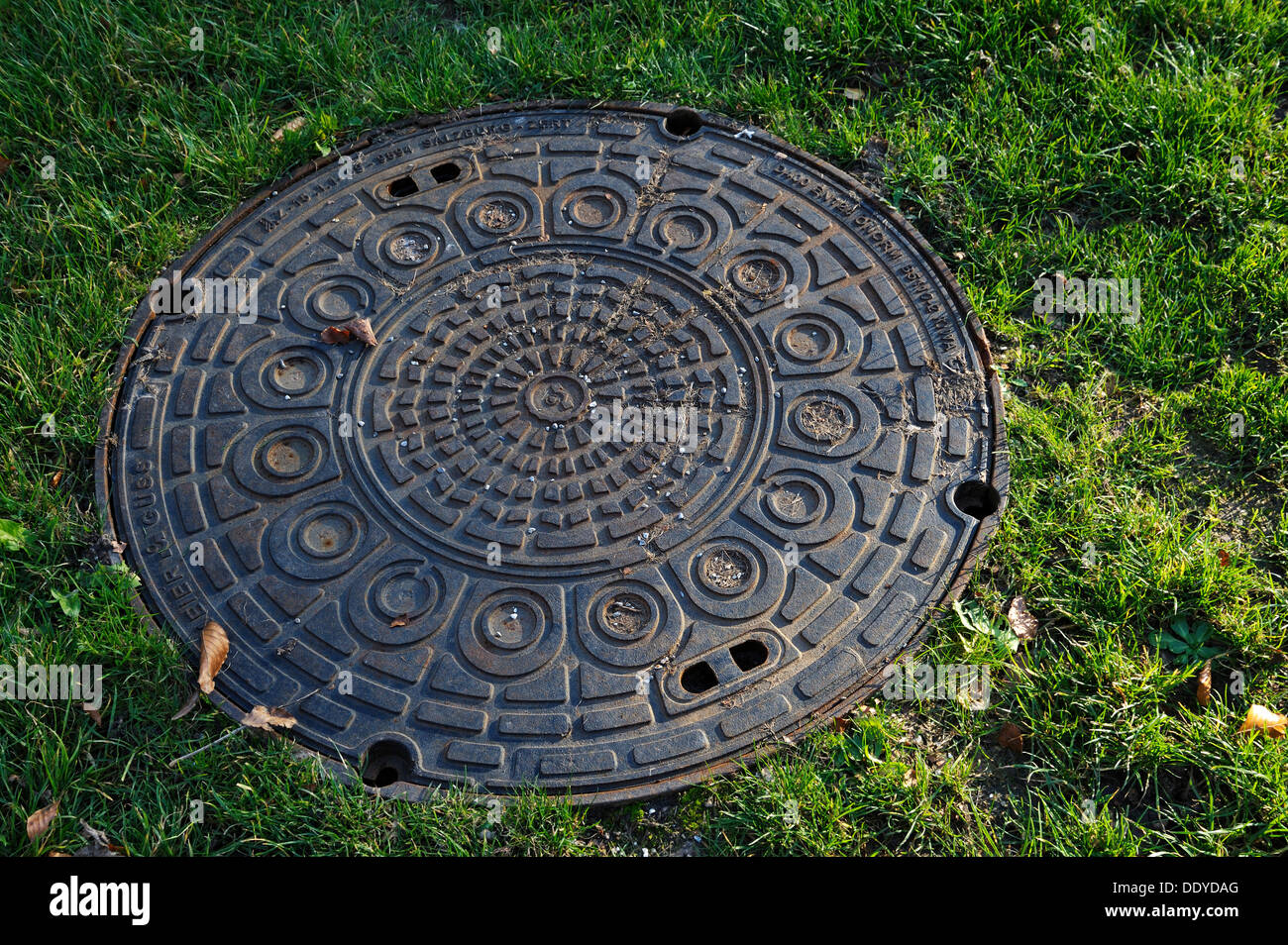 Manhole cover in the Ostfriedhof or East Cemetery, Munich, Bavaria - Stock Image