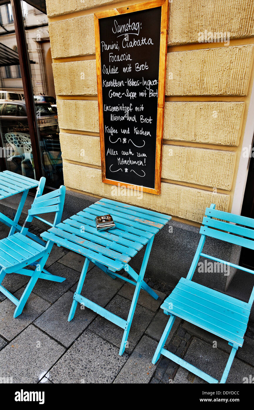 Street cafe with a menu board and blue tables and chairs, Munich, Bavaria - Stock Image