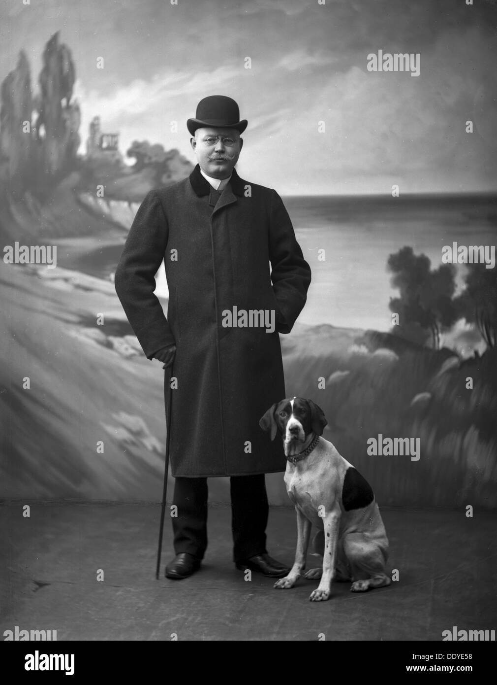 An elegant man wearing a black overcoat and a bowler hat posing with his dog in a photographer's studio, Landskrona, Sweden, 1910. From the Landskrona Museum Collection. - Stock Image
