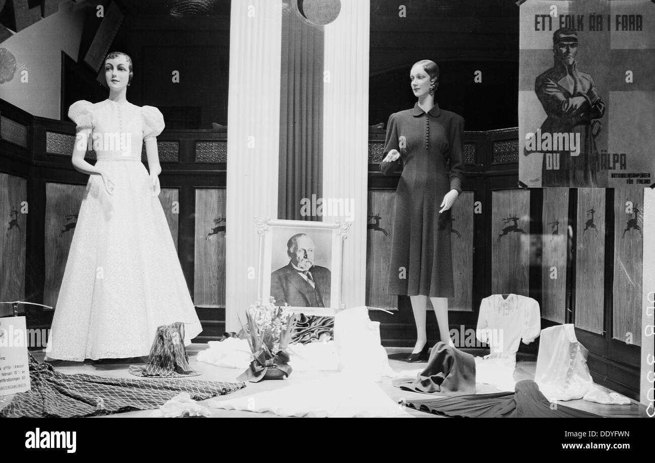 Clothes shop window with rwo mannequins, Malmö, Sweden, 1940. Note the pro-Finnish recruitment poster and the portrait of president Kallio. Although Sweden was officially non-belligerent during World War II, there was considerable popular support for Sweden's eastern neighbour Finland after the Soviet Union invaded in the Winter War in 1939. Sweden contributed financial and humanitarian aid to Finland, as well as Military supplies and equipment. In addition, some 8700 Swedes volunteered to fight alongside the Finns. From the Malmo Museum Collection. - Stock Image
