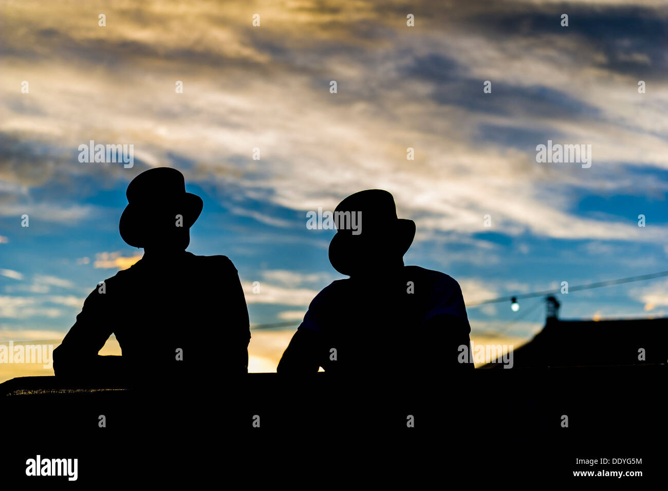 The silhouette of two festivalgoers wearing top hats at the Brownstock Festival in Essex. - Stock Image