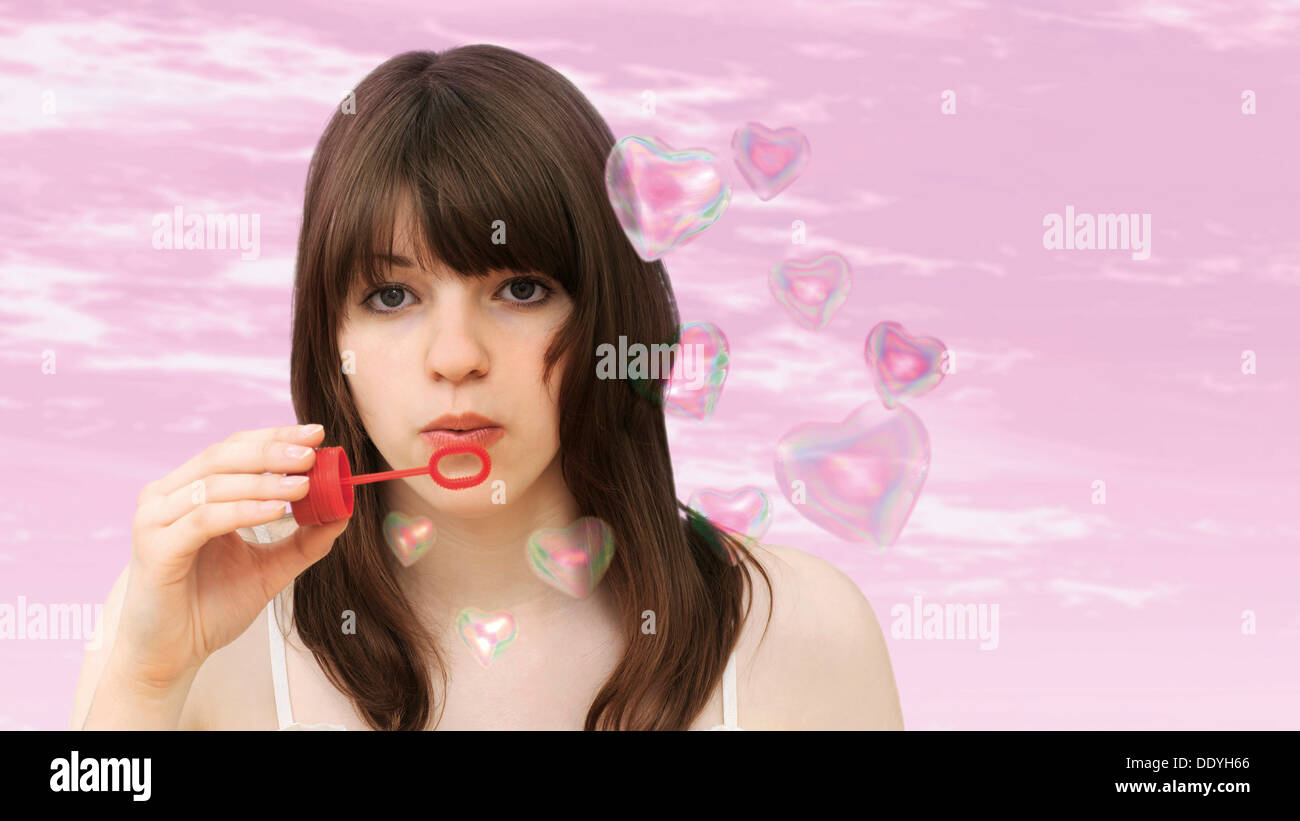 Young girl blowing heart-shaped soap-bubbles - Stock Image