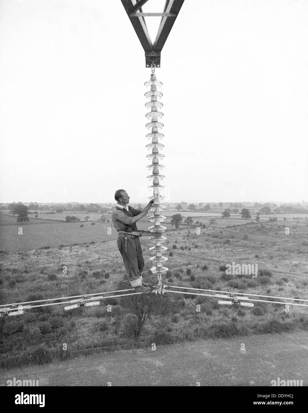 Electricity power insulator, cables and worker up a pylon, Nottinghamshire,c1950s-1960s(?). Artist: CEGB - Stock Image
