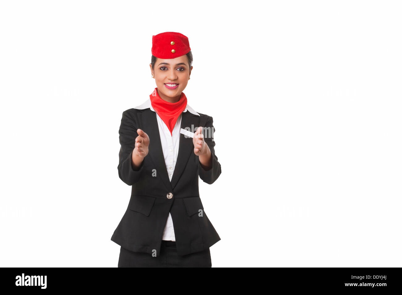 Flight attendant gesturing towards exits over white background - Stock Image
