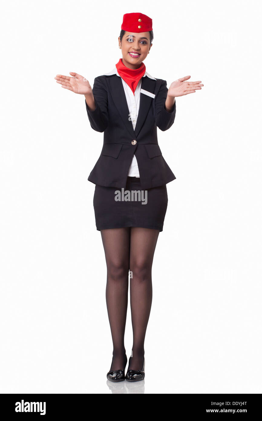 Portrait of young flight attendant gesturing over white background - Stock Image