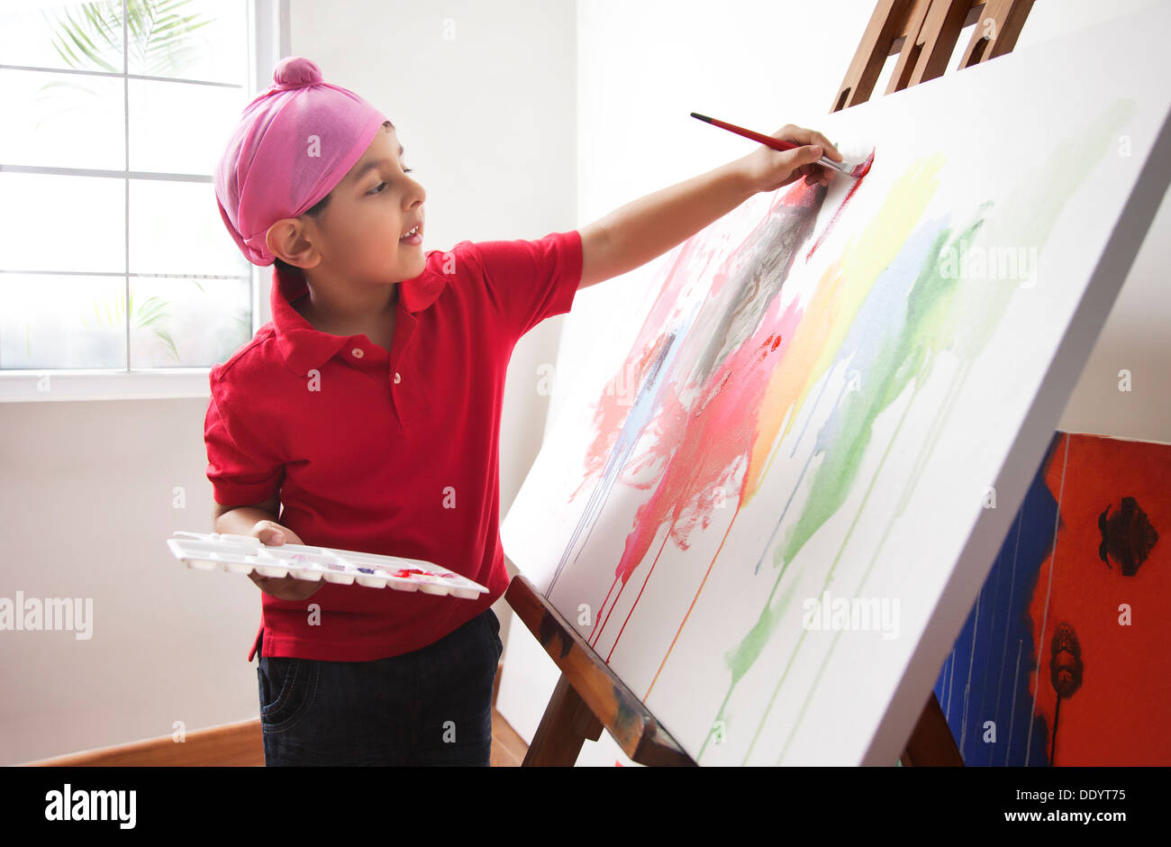 Cute little boy painting on artist's canvas - Stock Image