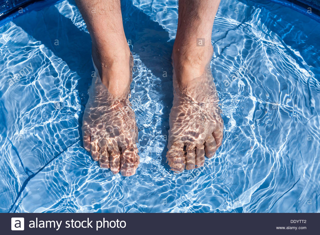 Cooling off feet in water - Stock Image