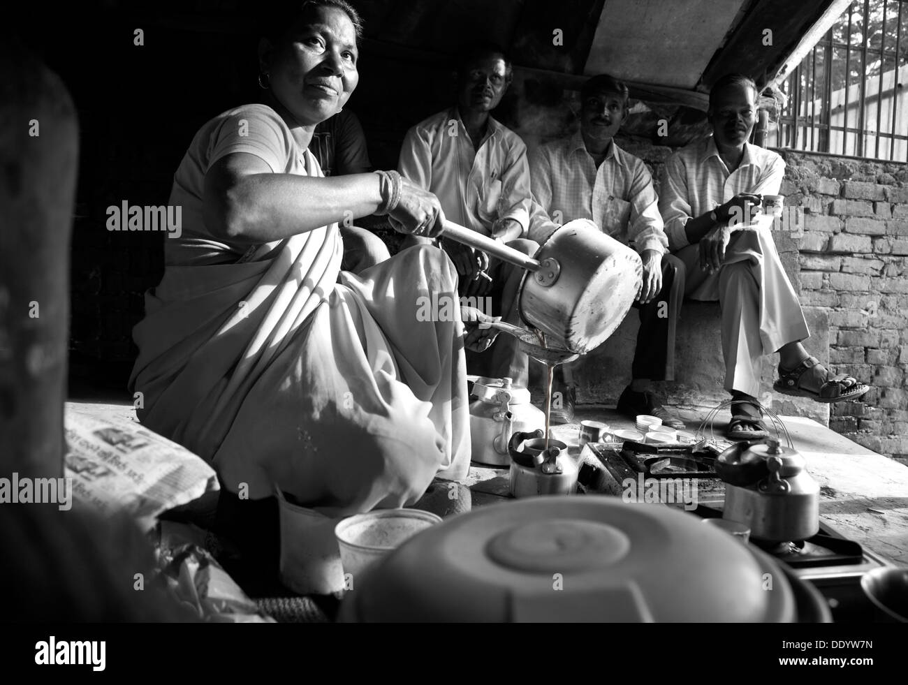 Black and white image of Indian female vendor pouring tea in kettle with customers sitting in background - Stock Image