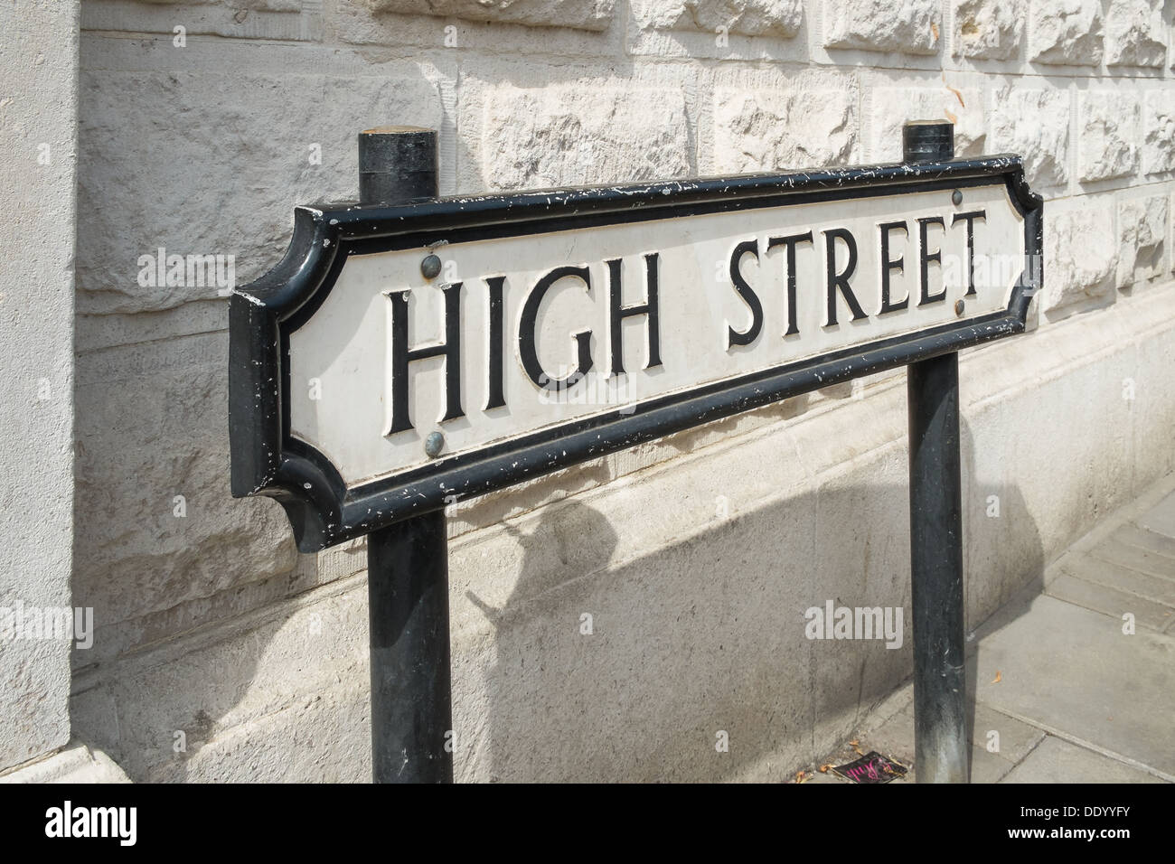 A High Street road sign in front of a white wall - Stock Image