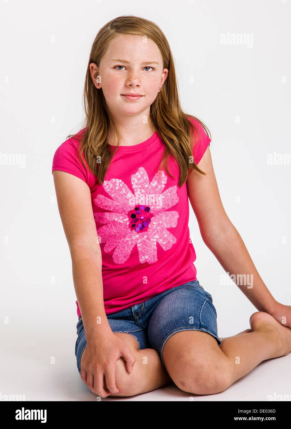 studio portrait of cute red haired ten year old girl stock photo