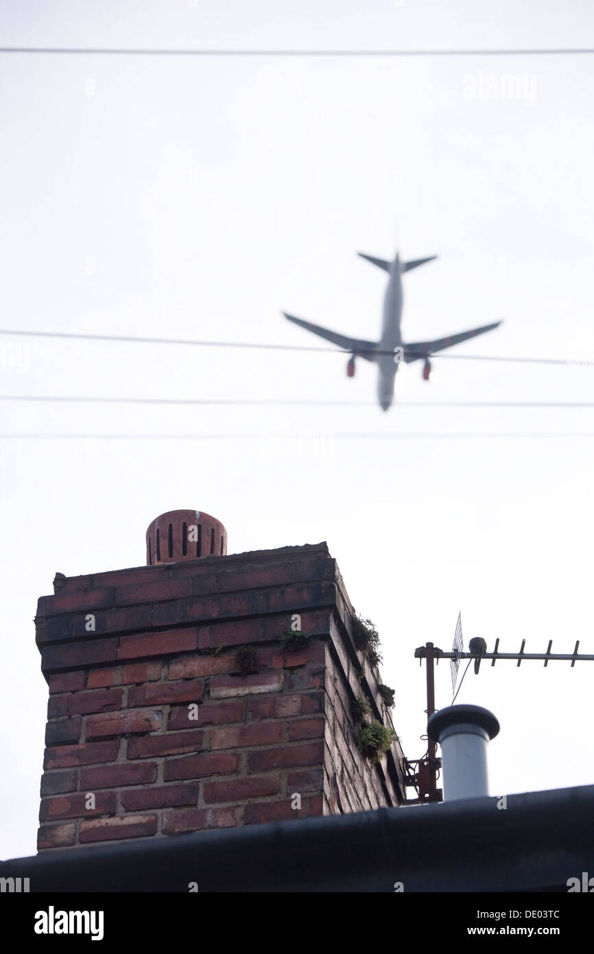 Airplane flying low over house roof top. - Stock Image