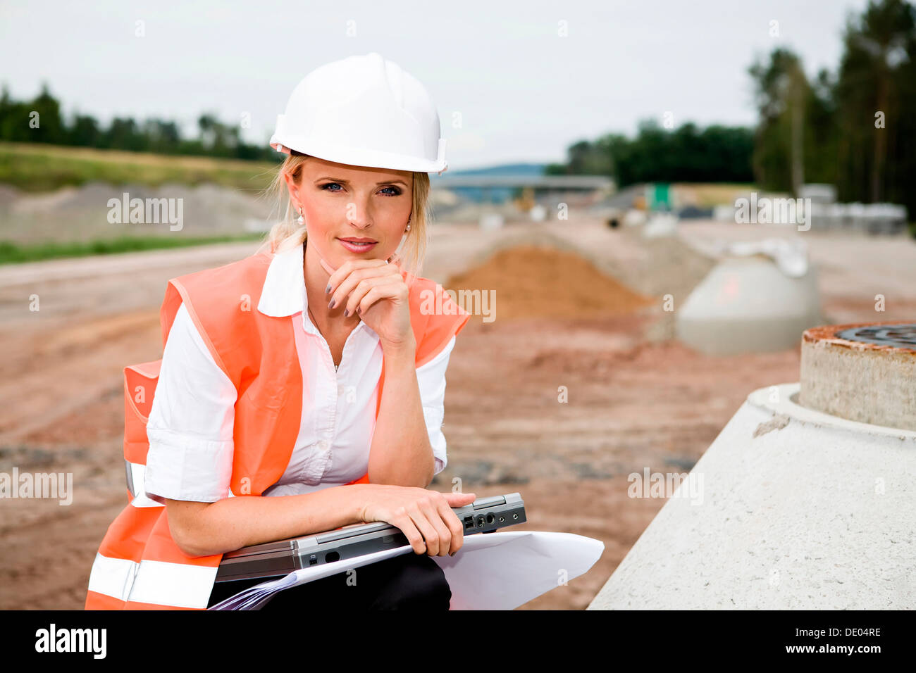 A young female constructor at building of a new motorway - Stock Image