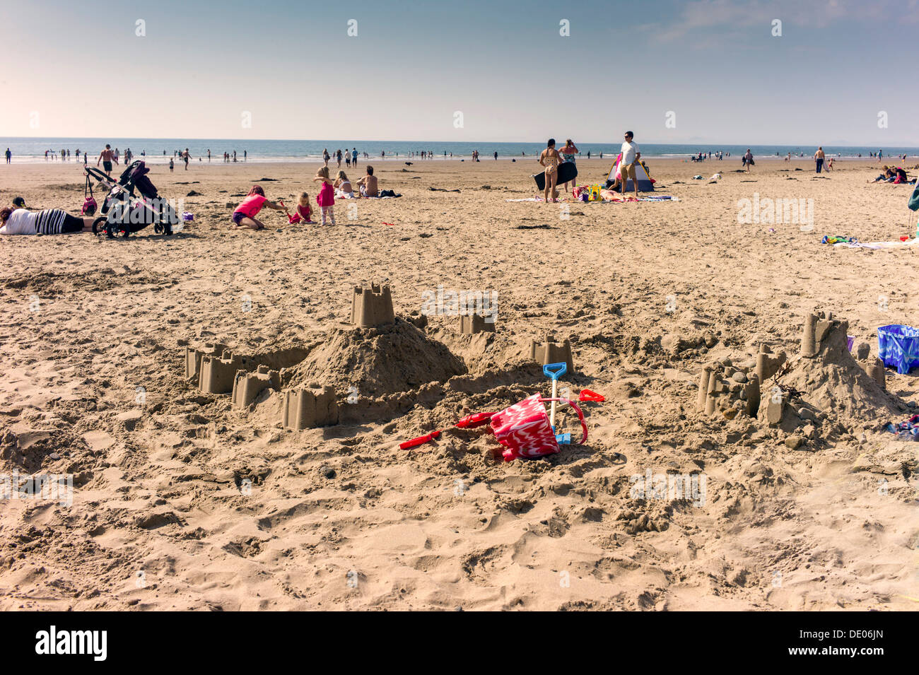 An abandoned childrens bucket and spade with newly made sand castle in the foreground, busy beach scene down to the sea - Stock Image