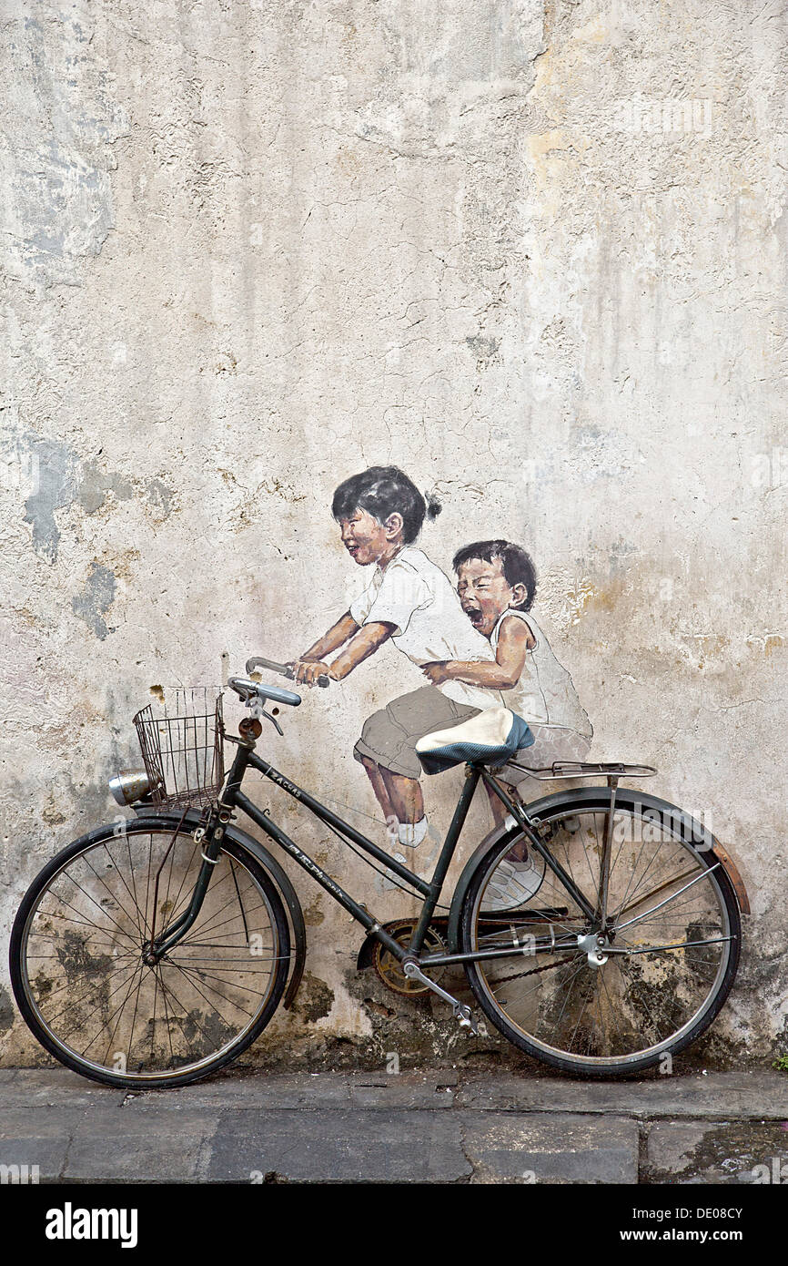 Bicycle in front of house wall with children painted as if they are riding the bike, street art - Stock Image