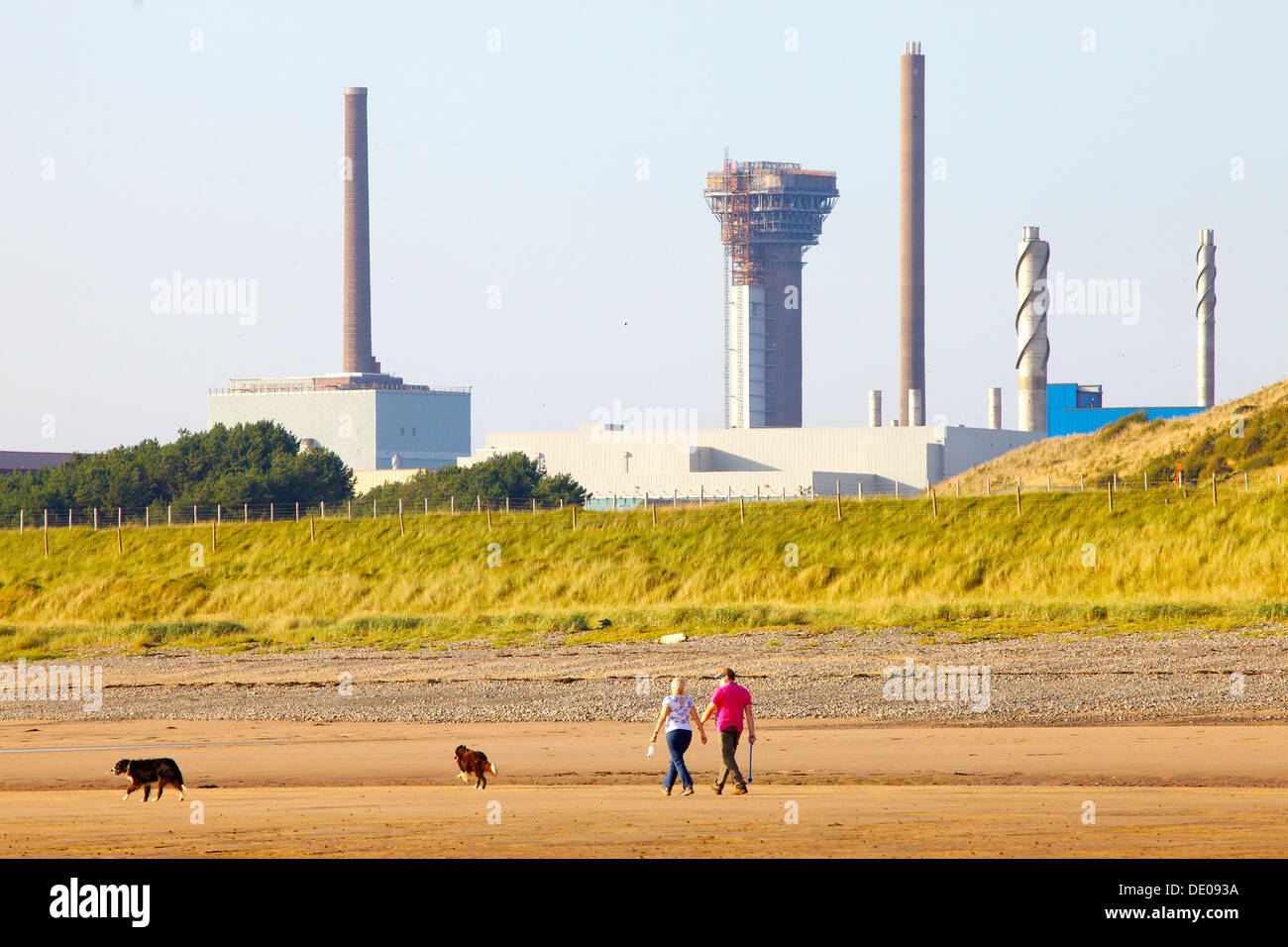 Sellafield nuclear power station with a couple walking their dogs on the sea shore in front Cumbria England United Kingdom - Stock Image