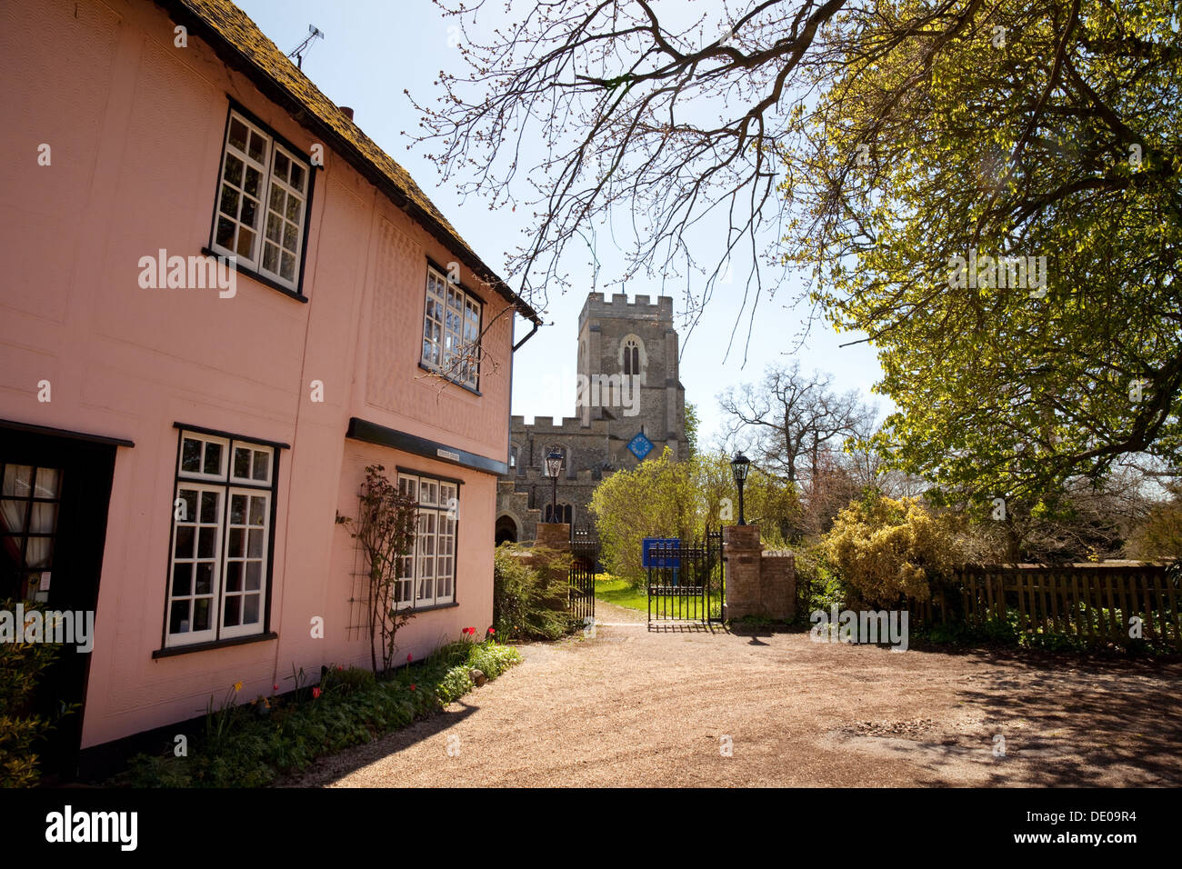Pink washed houses and Church of St John the Baptist, the village of Stoke by Clare, Suffolk, UK - Stock Image