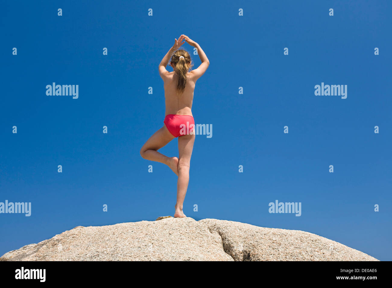 7-year-old girl doing Yoga on the rocks of Palombaggia beach, south-east coast, Balagne region, Corsica, France, Europe - Stock Image