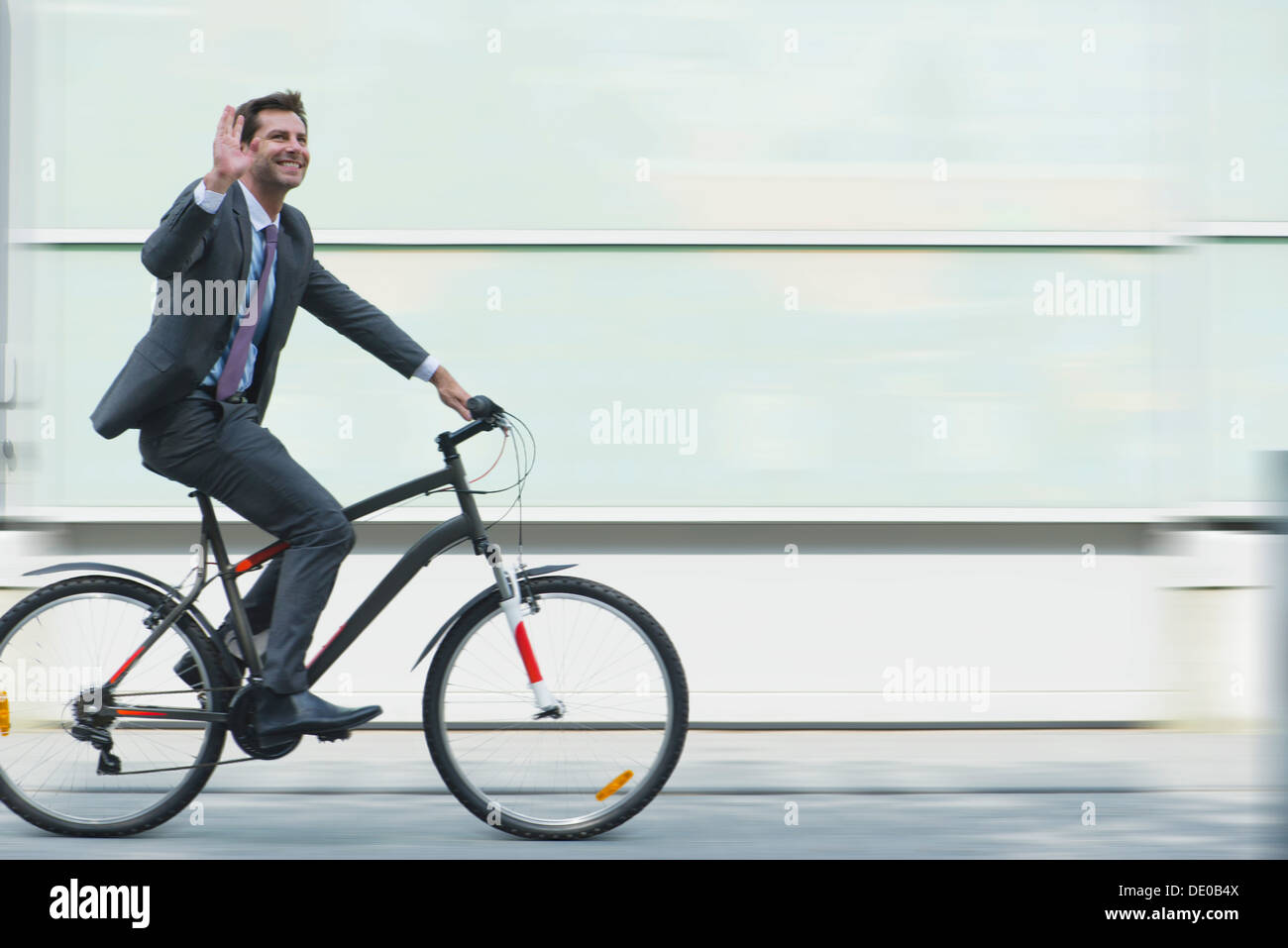 Businessman riding bicycle - Stock Image