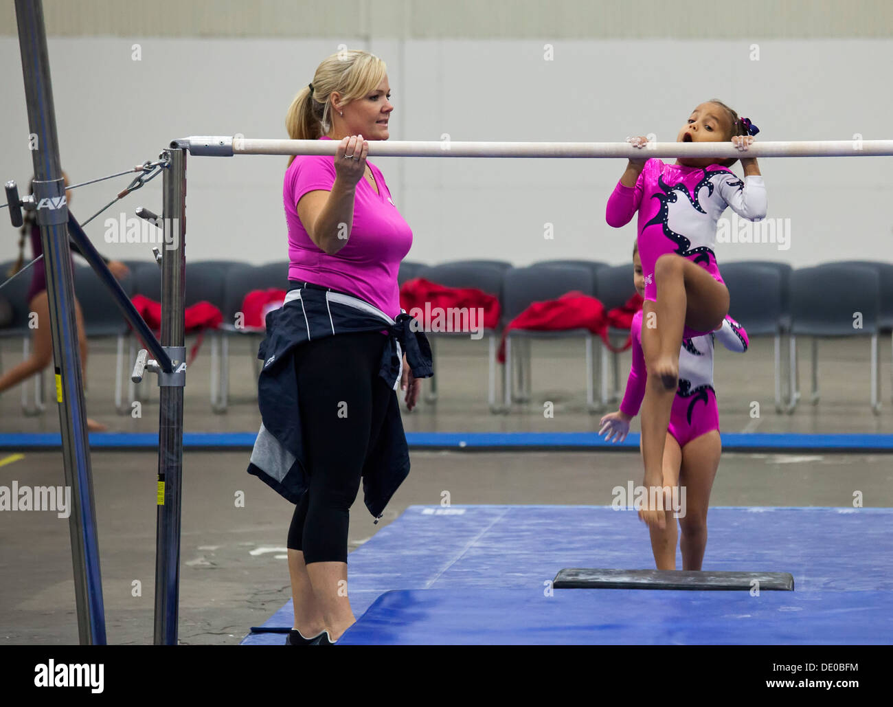 Detroit, Michigan - A coach watches as girls warm up on the parallel bars before competition in the AAU Junior Olympic Games. - Stock Image