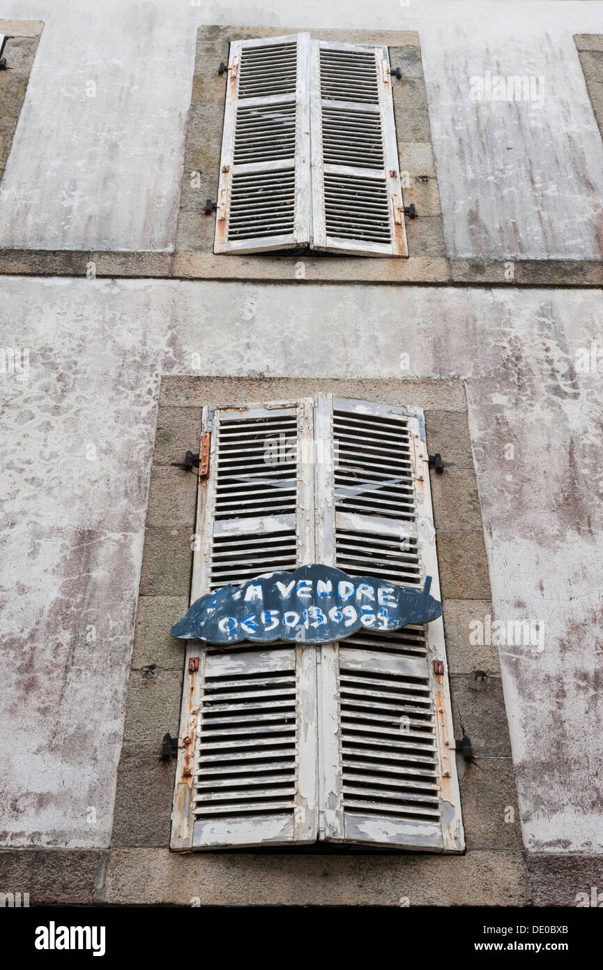 Old french shuttered windows on a building in Douarnenez Brittany France with for sale signs - Stock Image