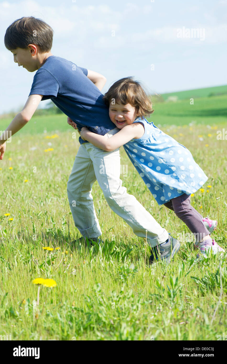 Young siblings playing together outdoors - Stock Image