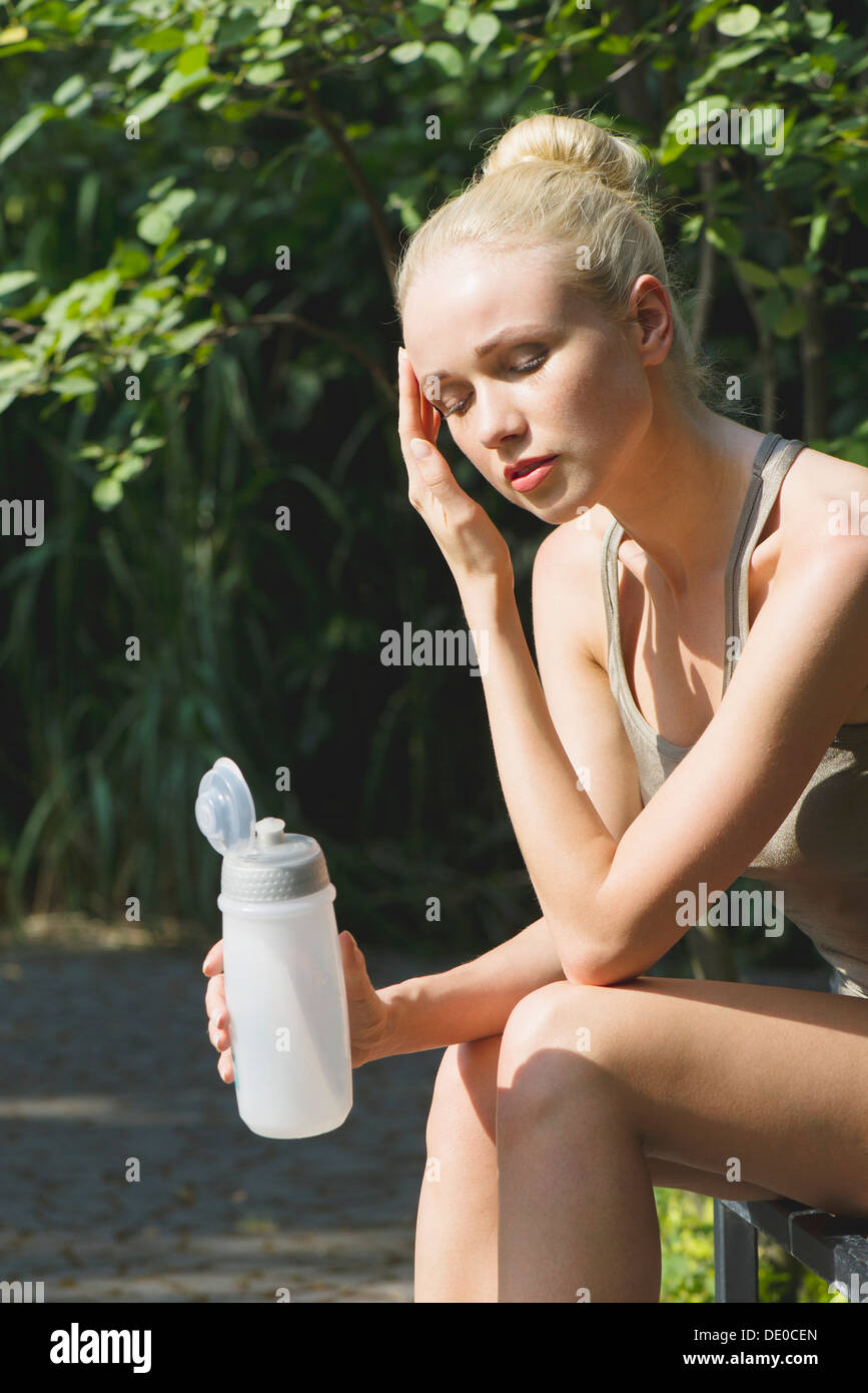 Young woman sitting outdoors with water bottle, eyes closed - Stock Image