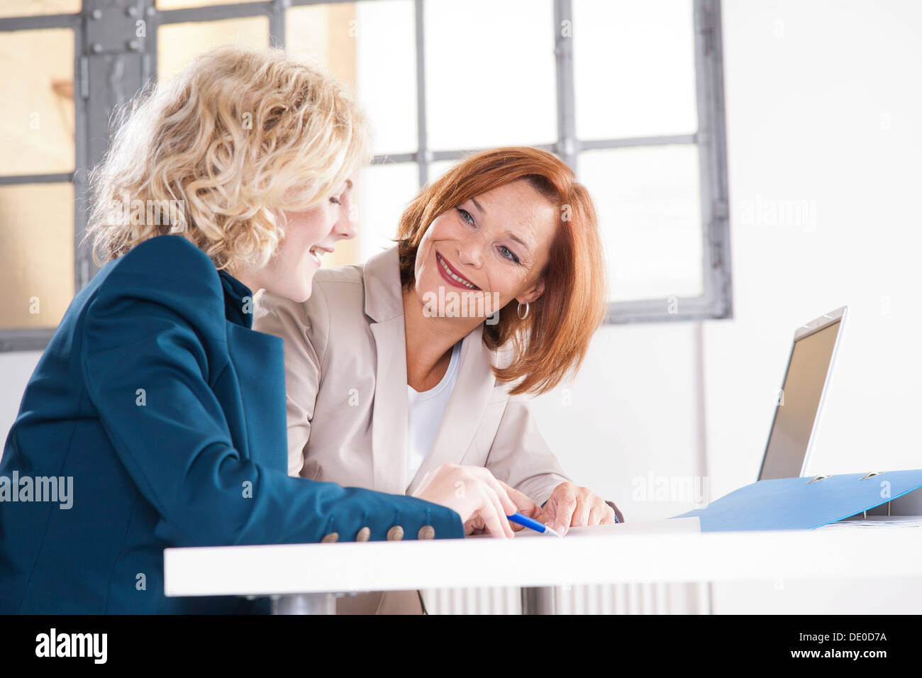 Manager working in an office with a trainee at the computer - Stock Image