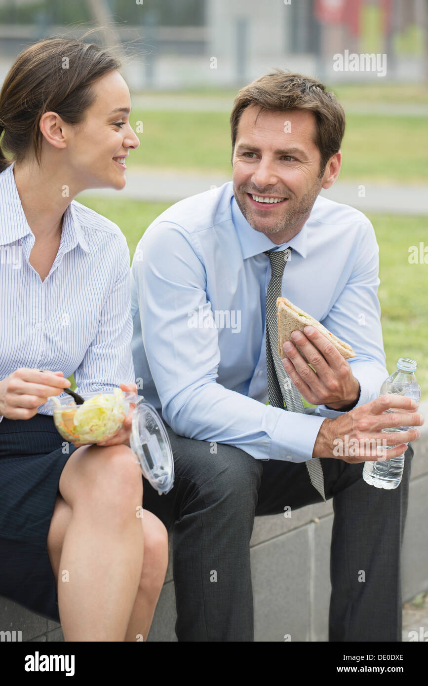 Coworkers having lunch together outdoors - Stock Image