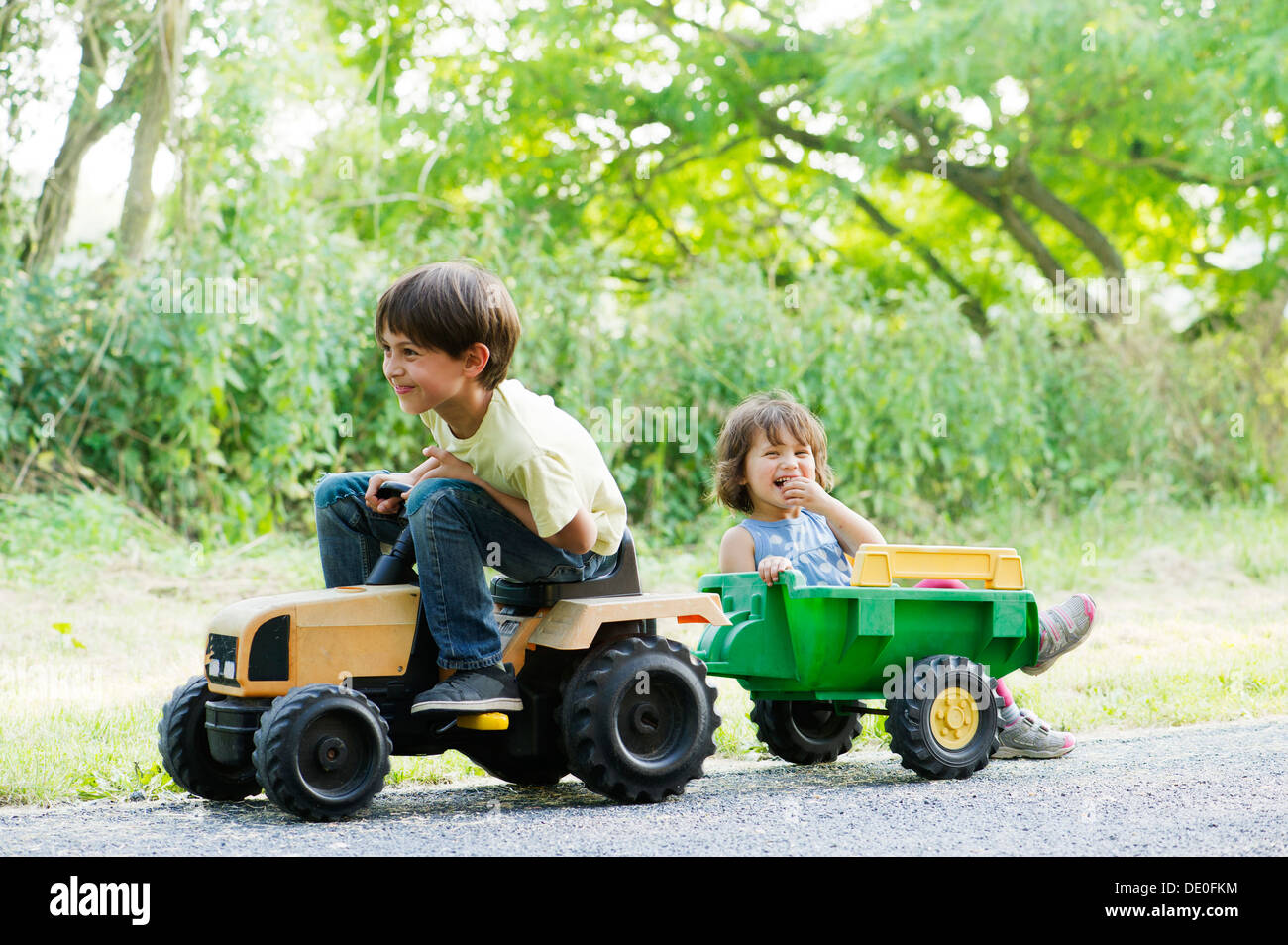 Young brother and sister riding on toy tractor - Stock Image