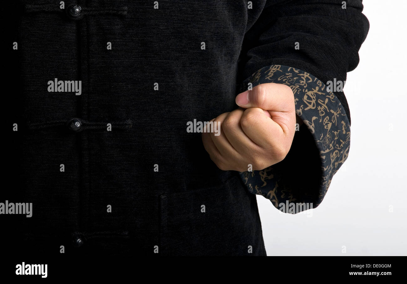 Combative fist of a Chinese Taiji Master, section of traditional jacket -  Stock Image
