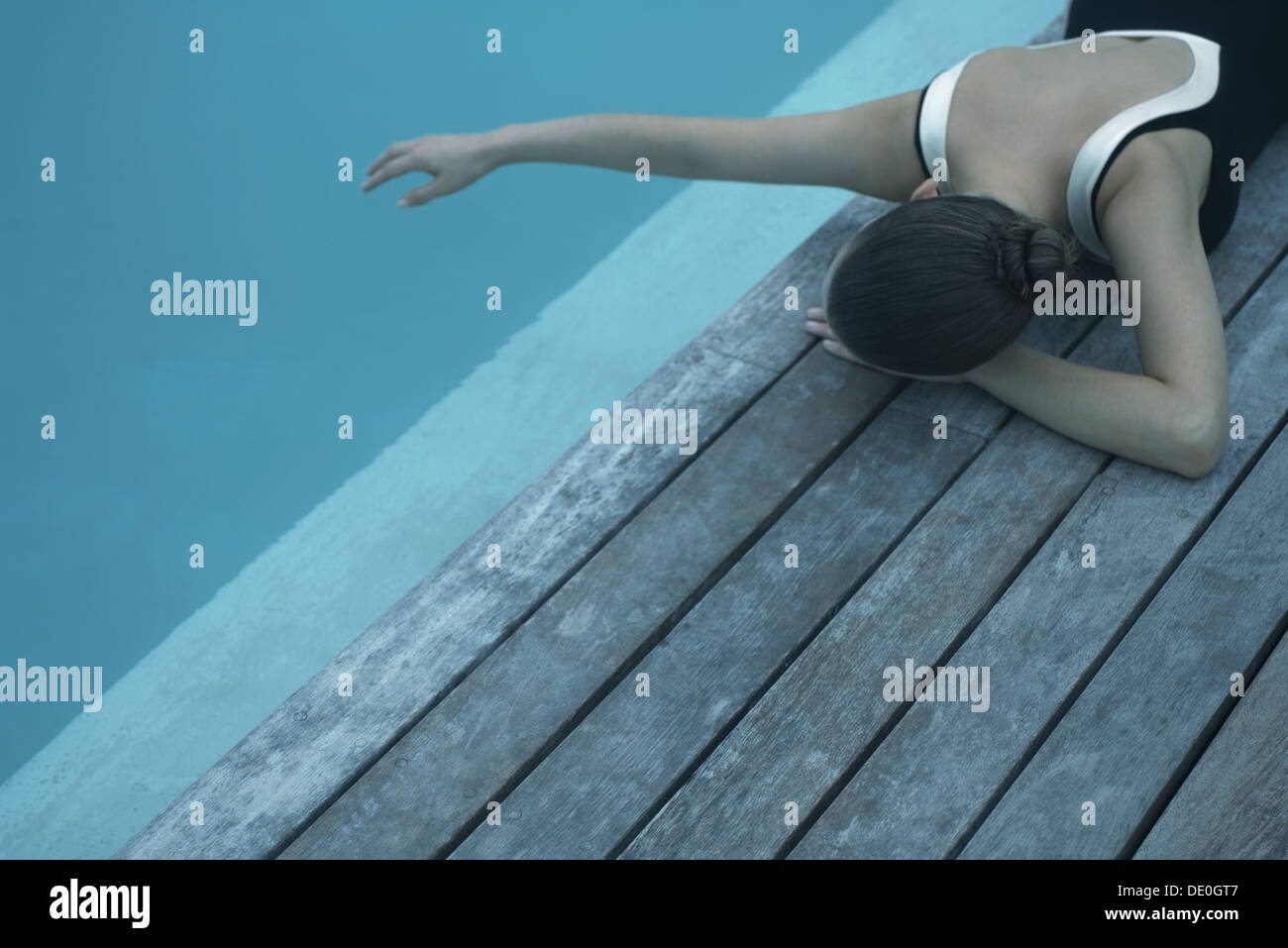 Woman in swimsuit lying on deck next to swimming pool, touching surface of water with hand - Stock Image