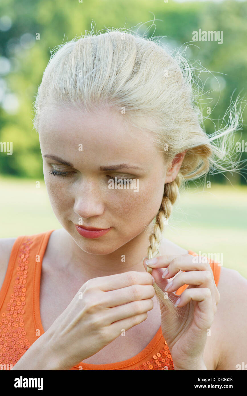 Young woman braiding hair, looking down in thought - Stock Image
