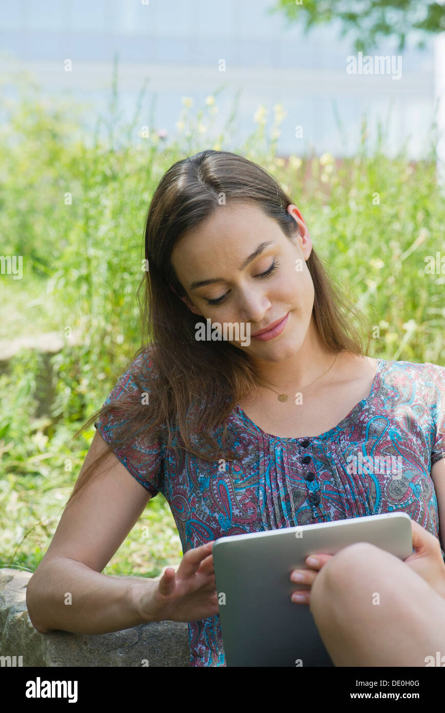 Woman using digital tablet outdoors - Stock Image