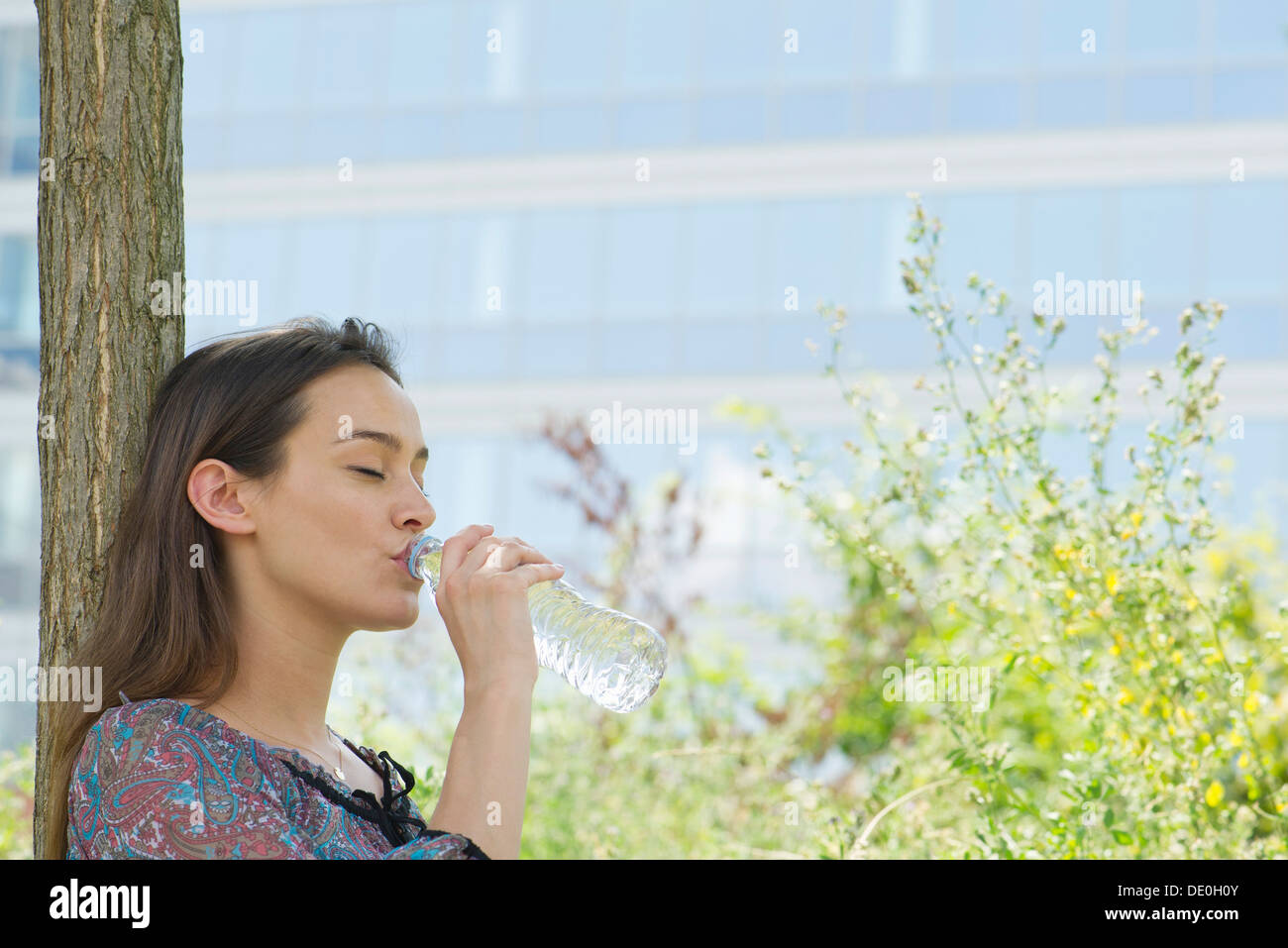 Woman drinking bottled water outdoors - Stock Image