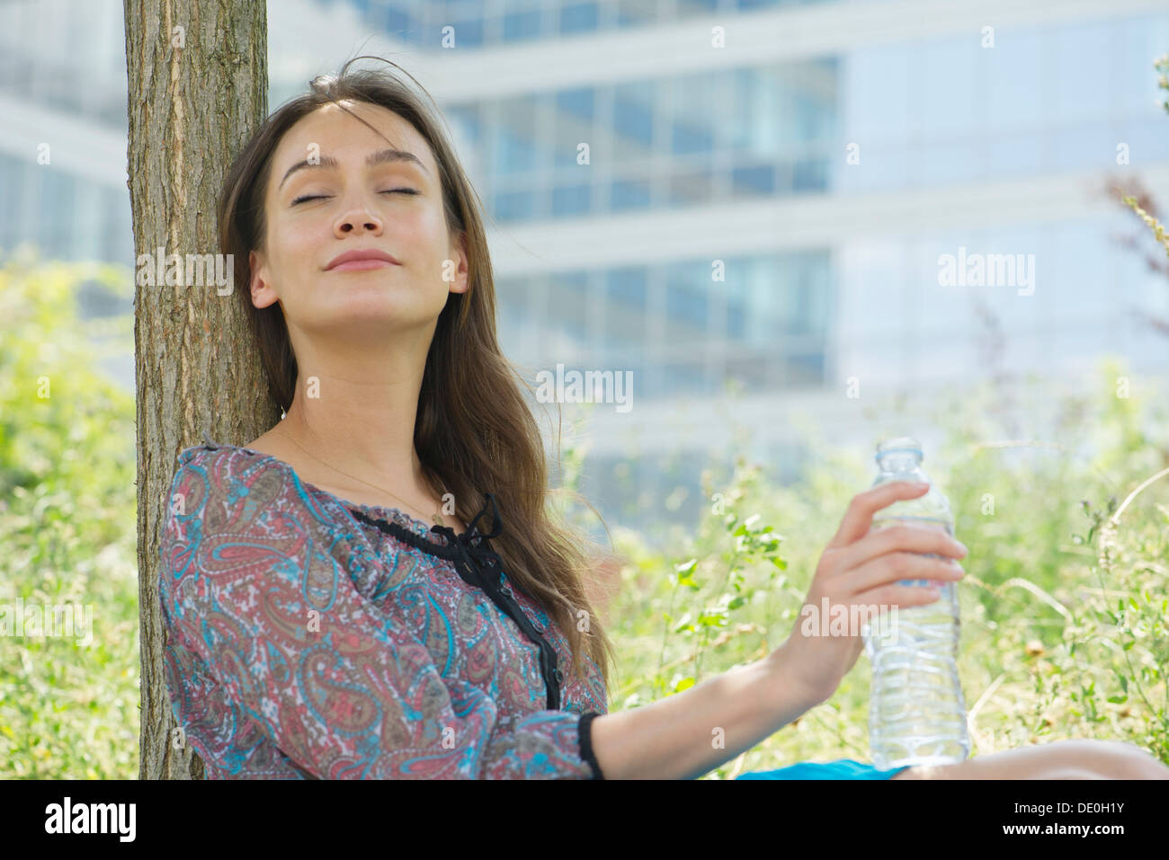 Woman relaxing outdoors with water bottle, eyes closed - Stock Image