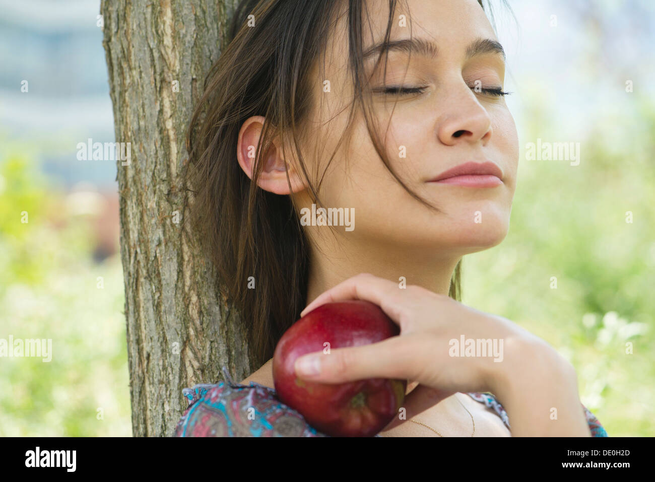 Woman relaxing outdoors with eyes closed, holding apple - Stock Image