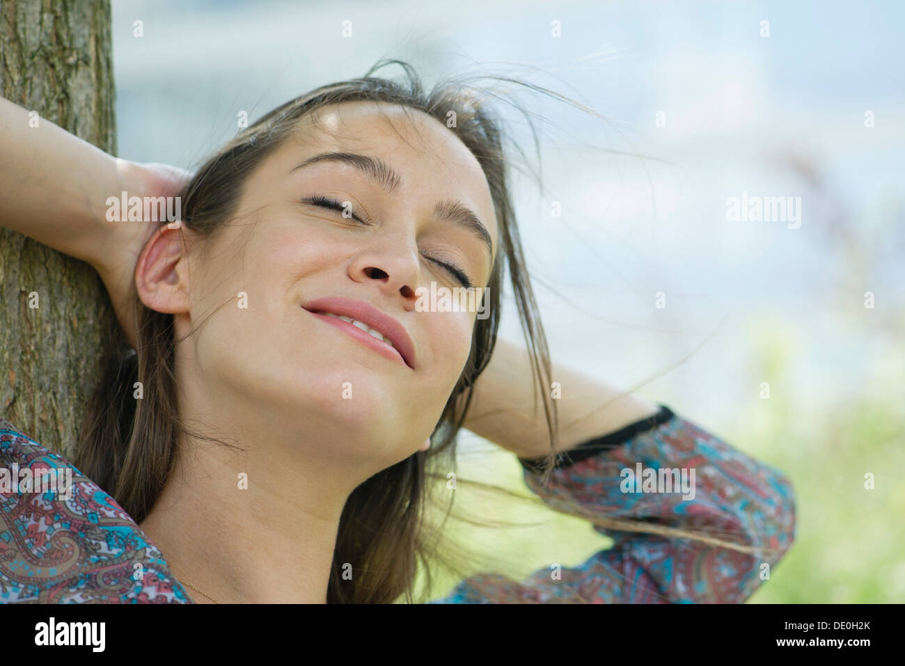 Woman relaxing outdoors, portrait - Stock Image