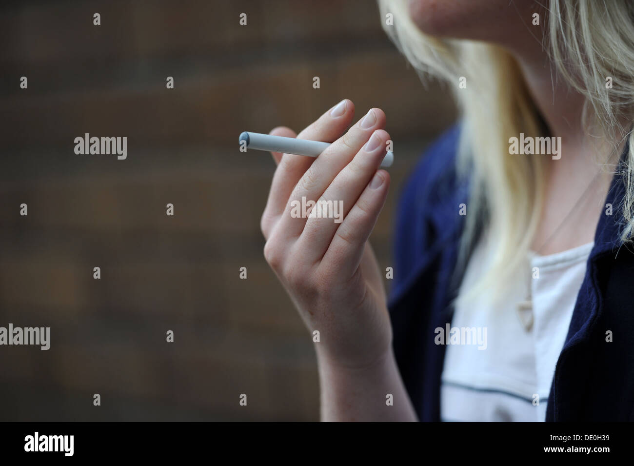 A girl holds an electronic cigarette in her hand. - Stock Image