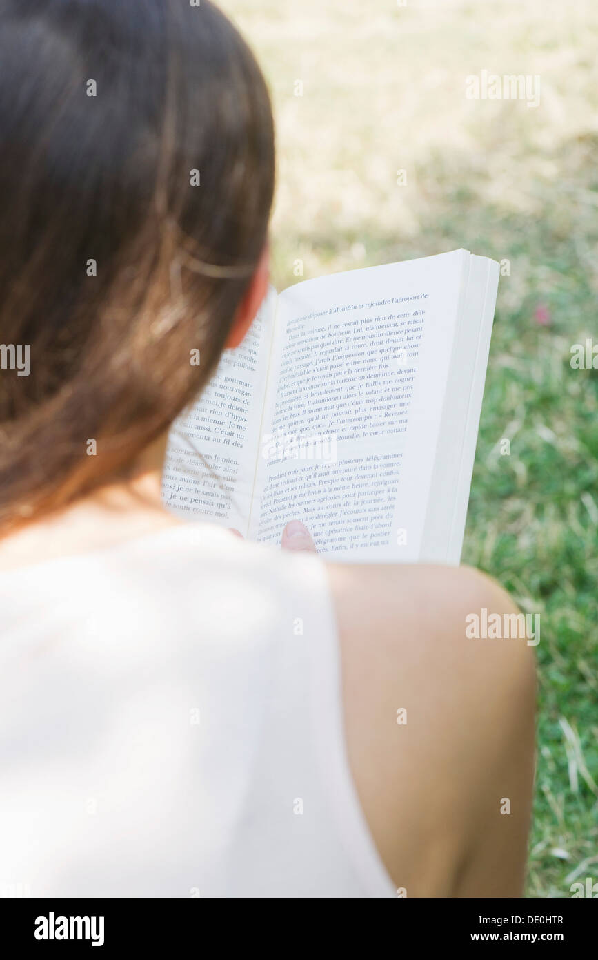 Woman reading book outdoors, over the shoulder view - Stock Image