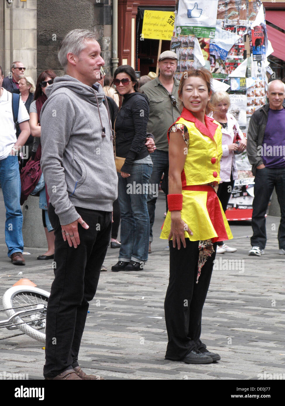 Chinese Woman Street Performer and Member of the Public Standing to Attention, The Royal Mile, Edinbrugh, Scotland, UK - Stock Image