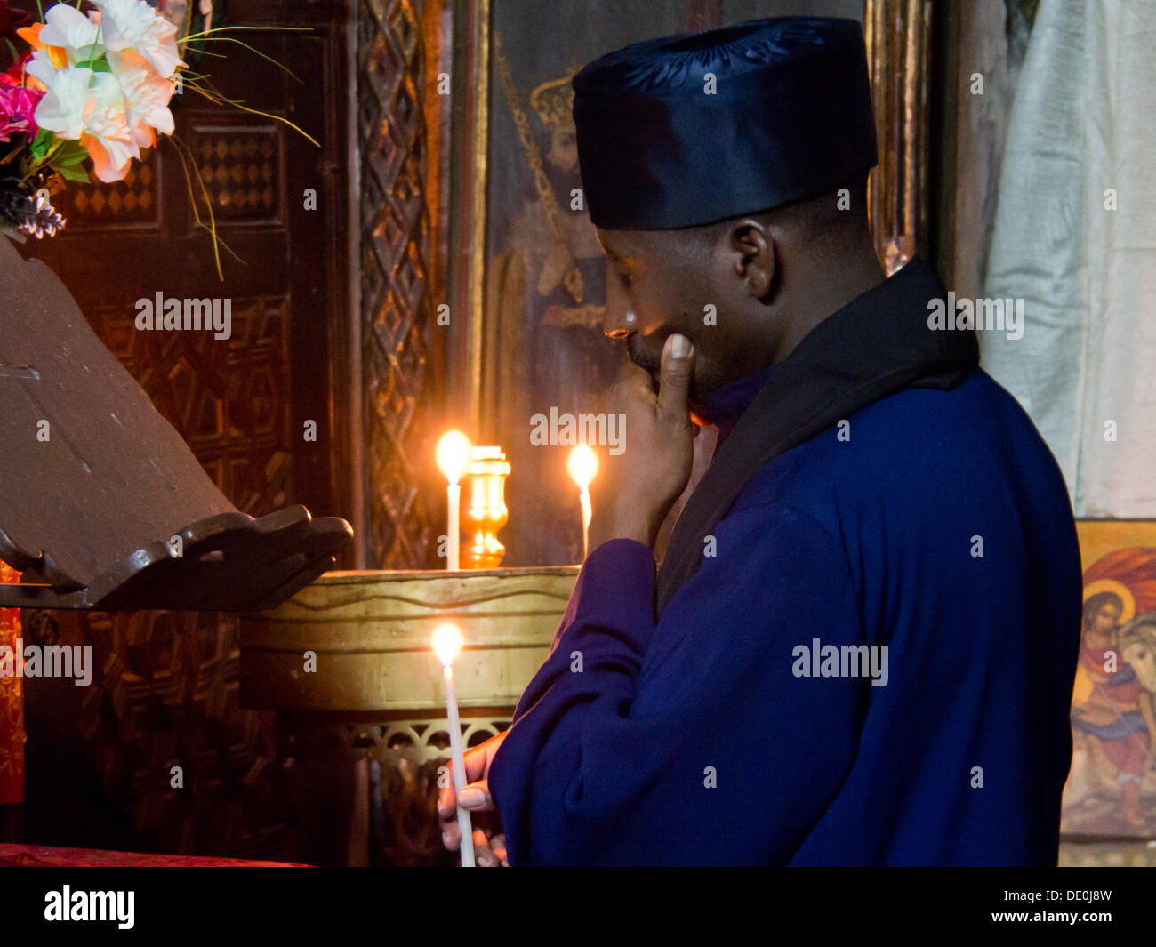 An Ethiopian priest in prayer in the Ethiopian Church adjacent to the Church of the Holy Sepulchre. Although legislation describes Israel as a 'Jewish' state it also provides for freedom of worship which is respected in practice. - Stock Image