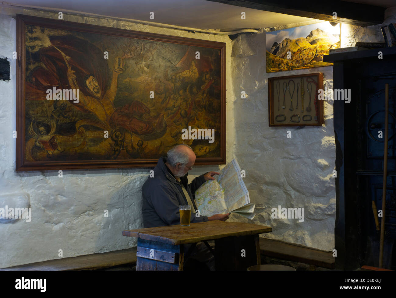 Elderly man reading Ordnance Survey map in climber's bar of the Old Dungeon Ghyll Hotel, Langdale, Lake District, Cumbria UK Stock Photo